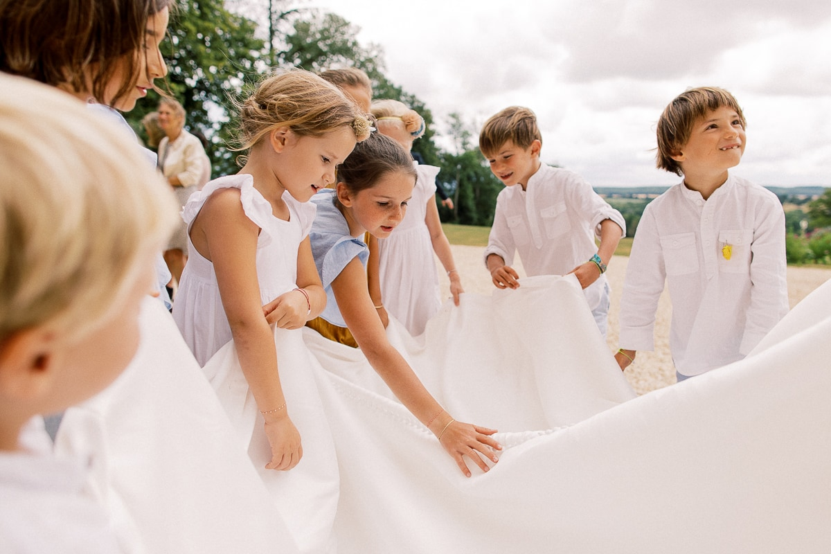 Children touch the bride's beautiful dress during the Bordeaux wedding cocktail party.
